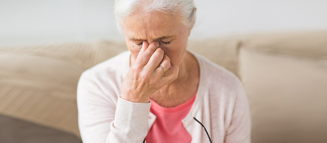 old age, health problem, vision and people concept - close up of senior woman with glasses sitting on sofa and having headache at home